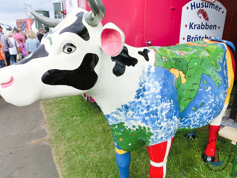 Schwarz-Bunte Kuh mit Landkarte auf dem Rücken